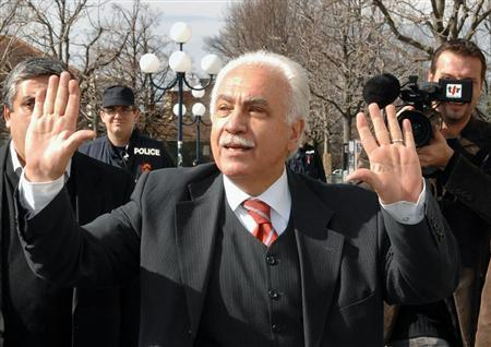 Turkish politician Perincek waves to supporters outside the court in Lausanne