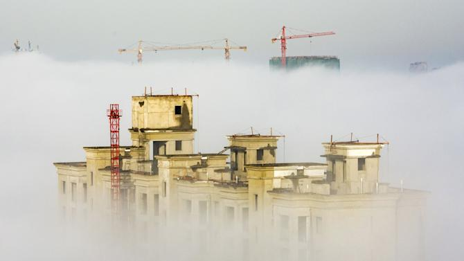 Cranes and residential buildings under construction are seen among thick fog in Anyang