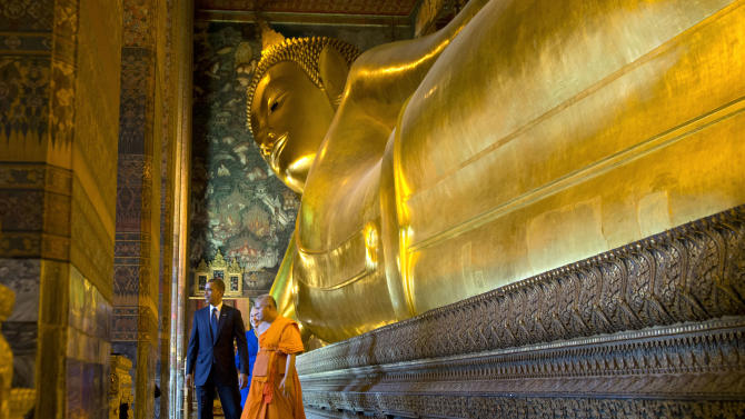 U.S. President Barack Obama, left, and U.S. Secretary of State Hillary Rodham Clinton, rear, tour the Viharn of the Reclining Buddha with Chaokun Suthee Thammanuwat, the Dean, Faculty of Buddhism Assistant to the Abbot of Wat Phra Chetuphon at the Wat Pho Royal Monastery in Bangkok, Thailand, Sunday, Nov. 18, 2012. (AP Photo/Carolyn Kaster)