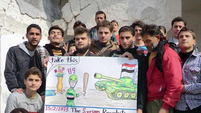 This citizen journalism image provided by Edlib News Network, ENN, which has been authenticated based on its contents and other AP reporting, shows anti-Syrian regime protesters holding a caricature placard during a demonstration, at Kafr Nabil town, in Idlib province, northern Syria, Friday, Feb. 15, 2013. Heavy fighting for control of the international airport in the northern Syrian city of Aleppo and a major military air base nearby has killed some 150 rebels and government soldiers over the past two days, activists said Friday. (AP Photo/Edlib News Network ENN)