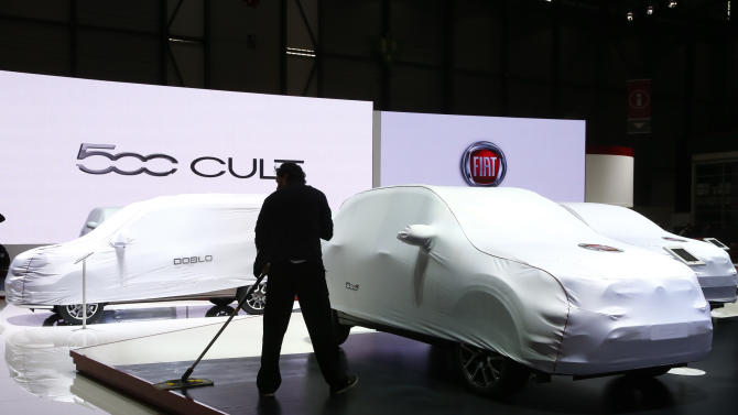 An employee cleans the FIAT booth ahead of the 85th International Motor Show in Geneva
