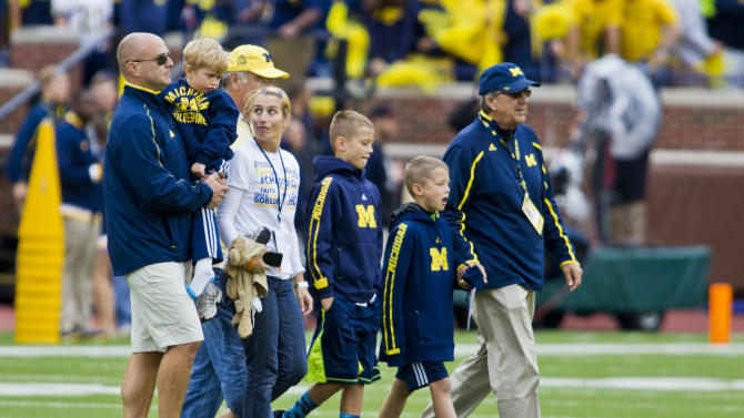 FILE - In this Sept. 12, 2015, file photo, former Michigan coach Lloyd Carr, far right, leads his grandsons T.J. and Tommy Carr, daughter-in-law Tammi Carr, and son Jason Carr, far left, holding his son Chad Carr, onto the Michigan Stadium field for the pregame coin toss, before an NCAA college football game against Oregon State in Ann Arbor, Mich. The 5-year-old grandson of former Michigan football coach Lloyd Carr has died more than a year after he was diagnosed with a rare, inoperable form of brain cancer. Chad Carr's father, Jason Carr, says his son died Monday, Nov. 23, 2015, in the family's Pittsfield Township home, where the boy had recently entered hospice care.  (AP Photo/Tony Ding, File)
