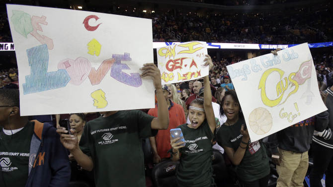Cleveland Cavaliers fans attending the NBA basketball team's scrimmage cheer and hold signs, Wednesday, Oct. 1, 2014, in Cleveland. (AP Photo/Tony Dejak)