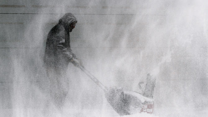Tom McReynolds clears snow from a neigbors' house in Wichita, Kans.,Thursday, Feb. 21, 2013. Kansas was the epicenter of the winter storm, with parts of Wichita buried under 13 inches of still-falling snow, but winter storm warnings stretched eastern Colorado through Illinois. (AP Photo/The Wichita Eagle, Jaime Greene)