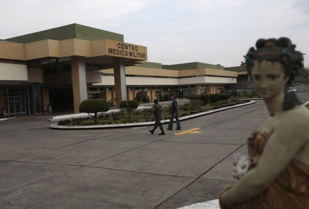 Soldier and man walk outside Centro Medico Militar where former Guatemalan dictator Rios Montt has been undergoing medical treatment in Guatemala City