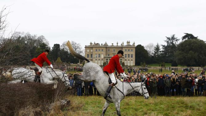 Spectators watch members of the Quorn Hunt jump a fence during the traditional Boxing Day meet at Prestwold Hall near Loughborough