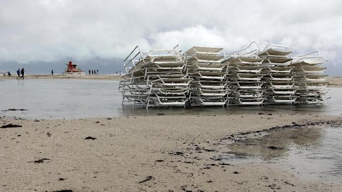 Unused beach chairs sit stacked up on the beach as Hurricane Sandy passes offshore to the east, Friday, Oct. 26, 2012, in Miami Beach, Fla. Hurricane Sandy left 21 people dead as it moved through the Caribbean, following a path that could see it blend with a winter storm and reach the U.S. East Coast as a super-storm next week. (AP Photo/Lynne Sladky)