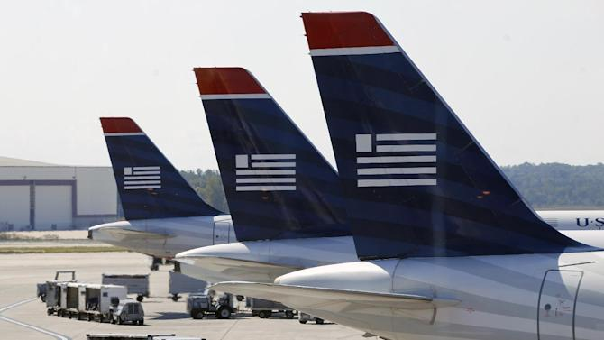 In this Thursday, Sept. 27, 2012, photo, US Airways jets are parked at their gates at the Charlotte/Douglas International airport in Charlotte, N.C. Patched together from several scrappy regional carriers on the brink of bankruptcy, US Airways has often been ridiculed within the aviation industry and remains a perennial afterthought among travelers. But it hopes to shed that image by merging with the larger  American Airlines, in a deal which will catapult the two to the top of the industry. (AP Photo/Chuck Burton