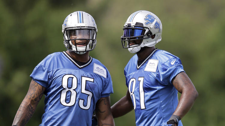 Detroit Lions tight end Eric Ebron (85) and Detroit Lions wide receiver Calvin Johnson talk during an NFL football training camp in Allen Park, Mich., Tuesday, July 29, 2014. (AP Photo/Paul Sancya)