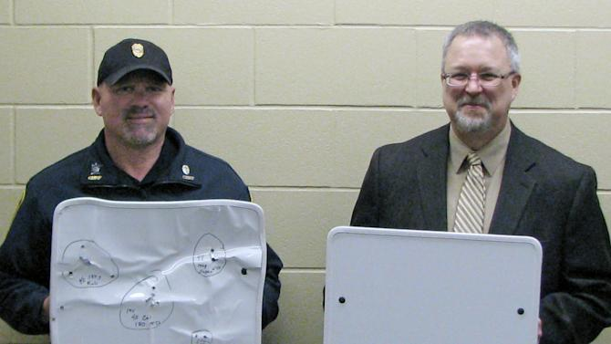 In this April 22, 2013 photo provided by the Cold Spring Record, Cold Spring Police Chief Phil Jones, left, and Rocori School District Superintendent Scott Staska pose with bulletproof white boards in Cold Spring, Minn. Rocori schools are among the first in the nation to acquire the kevlar whiteboards which can be flipped quickly to provide some protection for teachers and students in the event of a shooting. (AP Photo/Cold Spring Record, Mike Austreng)