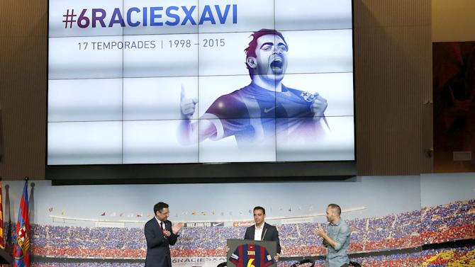 Barcelona's Xavi Hernandez shows the Barcelona jersey signed by the whole team between President Josep Maria Bartomeu and his teammate Andres Iniesta during his farewell event at Auditori 1899 in Nou Camp stadium in Barcelona