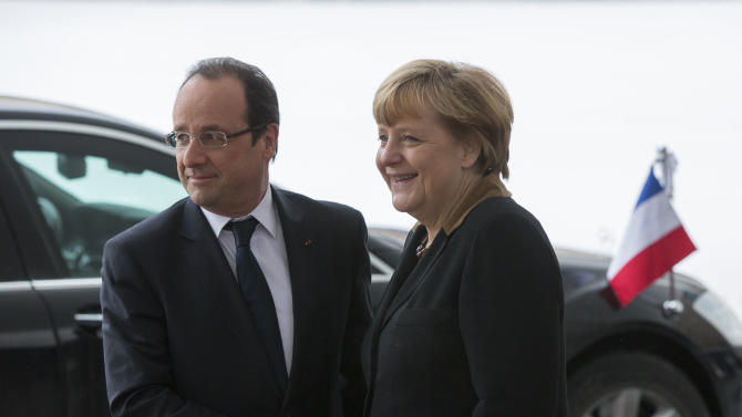German Chancellor Angela Merkel, right, welcomes French President Francois Hollande, left, at the Chancellery in Berlin, Germany, Tuesday, Jan. 22, 2013. France and Germany mark 50 years since they signed the Elysee Treaty, the post-war friendship pact between the former enemies. (AP Photo/Gero Breloer)