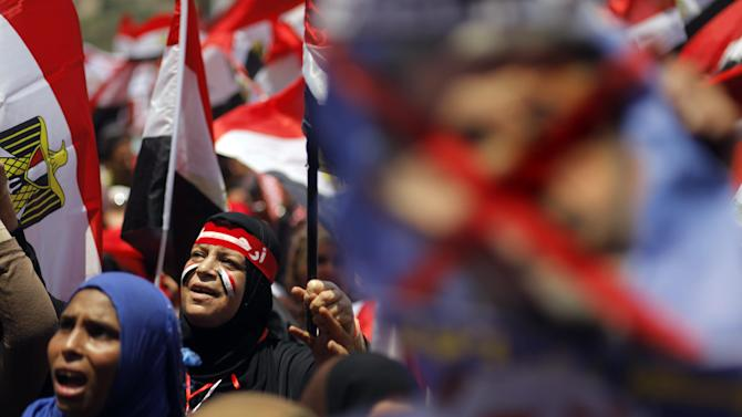 """Egyptian protesters chant slogans and hold anti-Egypt's Islamist President Mohammed Morsi poster during a rally in Tahrir Square, the focal point of Egyptian uprising, in Cairo Sunday, June 30, 2013. Organizers of a mass protest against Morsi claimed Saturday that more than 22 million people have signed their petition demanding the Islamist leader step down, asserting that the tally was a reflection of how much the public has turned against his rule. Arabic on the red scarf reads, """"Leave."""" (AP Photo/ Amr Nabil)"""