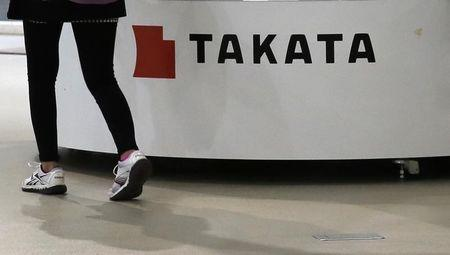 Visitor walks past displays of Takata Corp at a showroom for vehicles in Tokyo