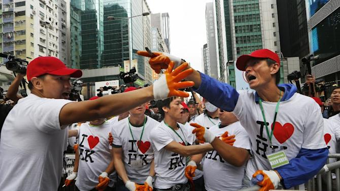 "People wearing ""I love Hong Kong"" T-shirts and red baseball caps argue with demonstrators as they help dismantle the first row of barricades made up mostly of wooden pallets by demonstrators after bailiffs issued a warning to the crowd that they would start enforcing the court-ordered clearance at an occupied area in Mong Kok district of Hong Kong Wednesday, Nov. 26, 2014. Hong Kong authorities cleared street barricades from a pro-democracy protest camp in the volatile Mong Kok district for a second day Wednesday after a night of clashes in which police arrested 116 people. The yellow banners with the words reading: ""I want genuine universal suffrage"". (AP Photo/Kin Cheung)"