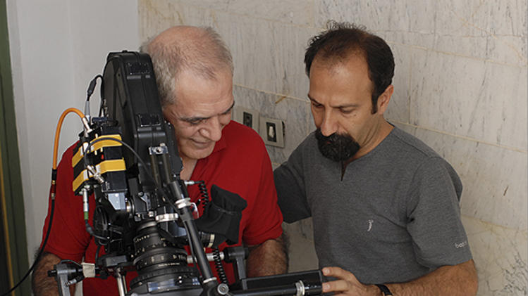 """In this undated photo released by Filmiran film distributing company, Iranian filmmaker Asghar Farhadi, right, looks through the screen next to his cameraman Mahmoud Kalari, at a scene of his movie """"A Separation"""" which won the Academy Awards in foreign films. Iran trumpeted the Islamic Republic's first foreign film Oscar win Monday as a triumph over archfoe Israel _ even as audiences in Israel packed theaters to watch the movie that beat their country's entry at the Academy Awards. (AP Photo/Filmiran International Company, Habib Majidi)"""