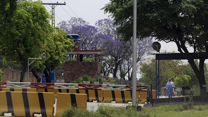 A woman walks near security barriers at the entrance of International School of Islamabad, in Islamabad