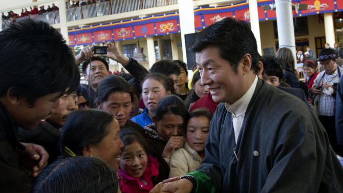 FILE - In this Dec. 10, 2011 file photo, Lobsang Sangay, front right, the prime minister of the Tibetan government in exile, greets people at a gathering in Dharmsala, India. Sangay came to power in what might be the most critical moment for Tibet in a generation: A wave of Tibetans have burned themselves alive to protest Chinese rule, Beijing is undergoing a transfer of power and the 76-year-old Dalai Lama is speaking openly of his eventual death. (AP Photo/Ashwini Bhatia, File)