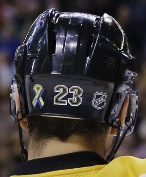 """FILE - In this April 17, 2013, file photo, Boston Bruins center Chris Kelly wears a """"Boston Strong"""" decal, left, on his helmet during an NHL hockey game against the Buffalo Sabres in Boston. With their """"Boston Strong"""" decals on the back of their helmets and the steady parade of Boston Marathon bombing victims honored at their games, the Bruins are hoping that a Stanley Cup victory will provide solace to those affected in the April 15 attacks. (AP Photo/Elise Amendola, File)"""