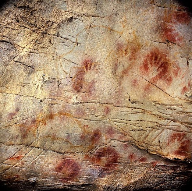 This undated handout photo provided by pedro suara/aaas shows detail of the 'Panel of Hands', El Castillo Cave showing red disks and hand stencils made by blowing or spitting paint onto the wall. A da