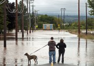 Residents take photos of a flooded area after dikes on the Salmon River gave way in Truro, Nova Scotia on Monday, Sept. 10, 2012. The area is under a rainfall warning as Tropical Storm Leslie churns toward Atlantic Canada. Leslie is expected to make landfall in Newfoundland bringing heavy rain and high winds. (AP Photo/The Canadian Press, Andrew Vaughan)