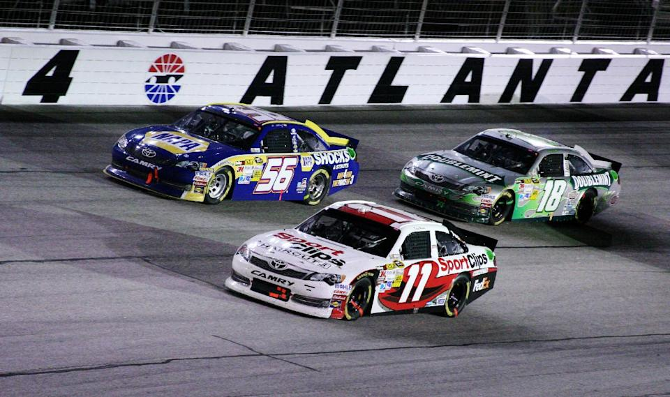 Denny Hamlin (11), Martin Truex Jr. (56) and Kevin Harvick (18) race through Turn 4 during the NASCAR Sprint Cup Series auto race at Atlanta Motor Speedway, Sunday, Sept. 2, 2012, in Hampton, Ga. (AP Photo/Dale Davis)