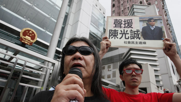 Pro-democracy protesters wearing sunglasses, display a placard with picture of  blind Chinese legal activist Chen Guangcheng outside the China's Liaison Office in Hong Kong Monday, April 30, 2012 as they urge Beijing government stop persecution of Chen. A U.S. rights campaigner says a deal securing U.S. asylum for a blind Chinese legal activist who fled house arrest is expected in the coming 24 to 48 hours.  (AP Photo/Kin Cheung)