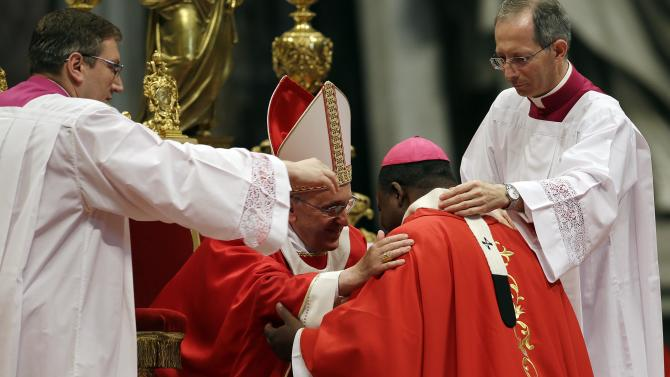 Monsignor Dieudonne Nzapalainga, of the Central African Republic, is greeted by Pope Francis after receiving the Pallium, a woolen shawl symbolizing his bond to the pope, during a mass in St. Peter's Basilica, at the Vatican, Saturday, June 29, 2013. (AP Photo/Gregorio Borgia)