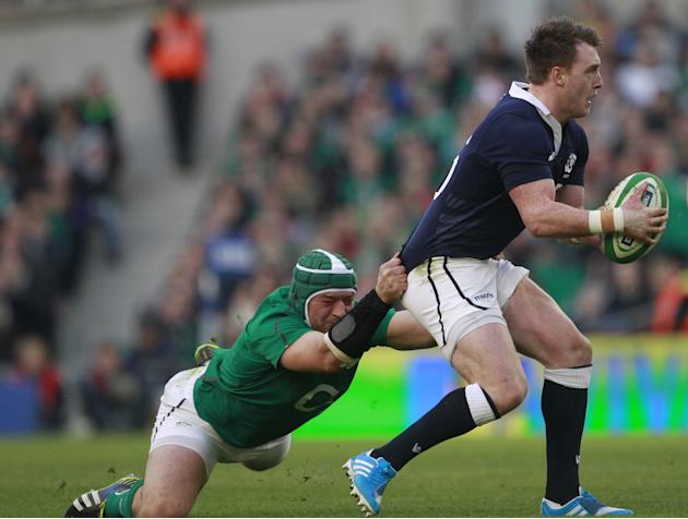 Scotland's Stuart Hogg, right, is tackled by Ireland's Rory Best during their Six Nations Rugby Union international match at the Aviva Stadium, Dublin, Ireland, Sunday, Feb. 2, 2014. (AP Photo