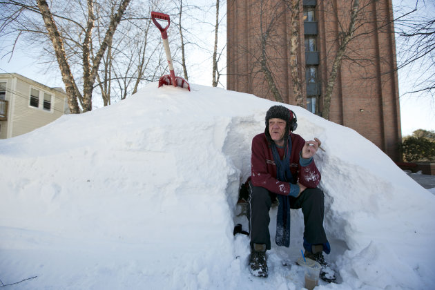 Bert Johnson takes a break while clearing snow from a bus-stop bench outside the apartment complex where he lives in Portland, Maine, Sunday, Feb. 10, 2013. Residents are digging out after a blizzard 
