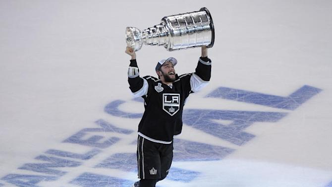 Los Angeles Kings defenseman Alec Martinez carries the Stanley Cup after beating the New York Rangers in Game 5 of the NHL Stanley Cup Final series Friday, June 13, 2014, in Los Angeles. The Kings won, 3-2, with Martinez scoring the winning goal in double overtime