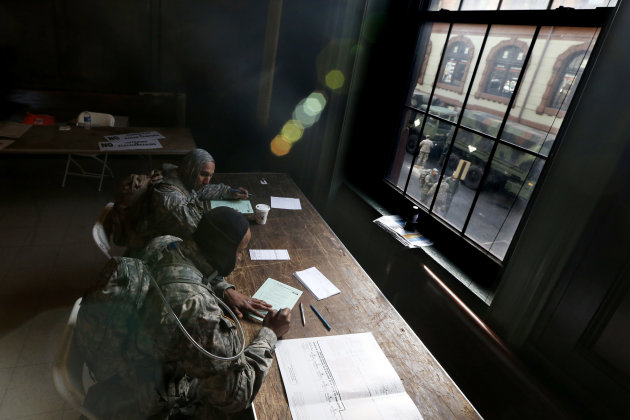 With members of the New Jersey National Guard seen through a window as they congregate outside of Hoboken City Hall, specialists Abdul Scott, bottom right, of Elizabeth, N.J., and Cullin King, of Hill