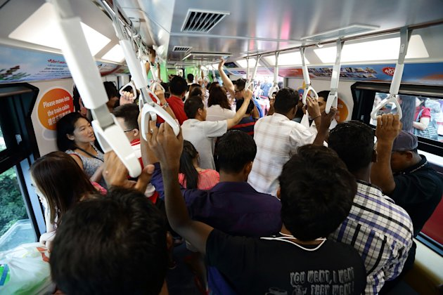 SINGAPORE - FEBRUARY 13: People packed the Sentosa Express train on February 13, 2013 in Singapore. The government white paper revealed Singapore's population may increase 30% to over 6.9 million by 2030, with nearly half the population expected to be foreign-born. Many local residents are critising the plan concerned about the added strain on housing, transportation and healthcare and the diminishing identity of the Singaporean community. (Photo by Suhaimi Abdullah/Getty Images)