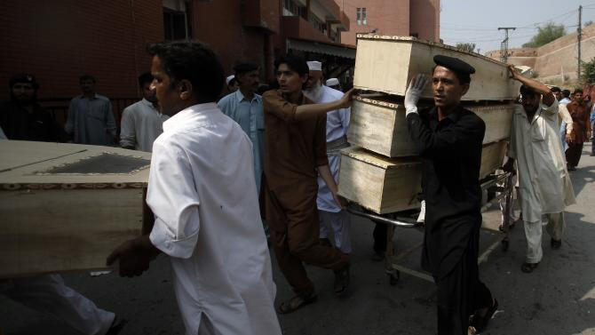 Hospital staff carry coffins after a bomb blast, at a hospital in Peshawar
