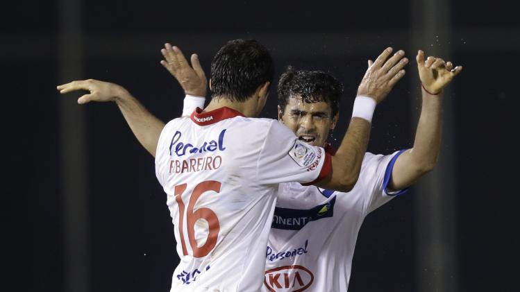 Julian Benitez of Paraguay's Nacional, right, celebrates with temamate Fredy Bareiro after scoring against Argentina's Velez Sarsfield during a Copa Libertadores game in Asuncion, Paraguay, Wednesday, April 23, 2014. (AP Photo/Jorge Saenz)