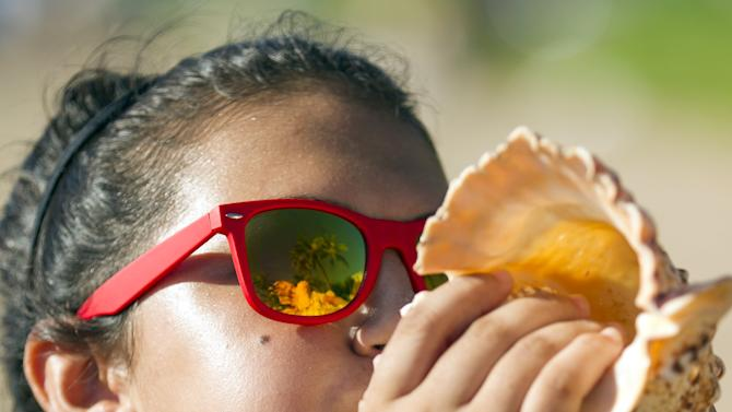 Emmy Kealoha, 13, blows a conch shell in protest of the Trans-Pacific Partnership (TPP) meeting held in Lahaina, Maui