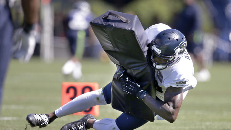Seattle Seahawks' Phillip Adams brings down a pad at an NFL football camp practice Wednesday, July 30, 2014, in Renton, Wash
