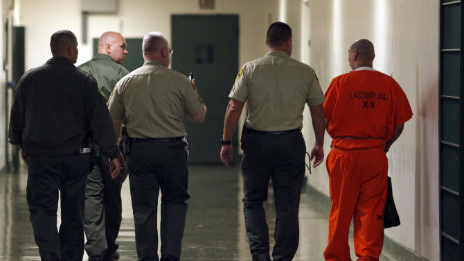 A team of Los Angeles County Sheriff's deputies, including one with a video camera, center, escort a Level 10 inmate, described as the highest security level requiring monitoring and supervision, at the Men's Central Jail in downtown Los Angeles Wednesday, Oct. 3, 2012. Los Angeles County Sheriff Lee Baca says he plans to implement all the reforms suggested by a commission in the wake of allegations that a culture of violence flourished in his jails. (AP Photo/Reed Saxon)