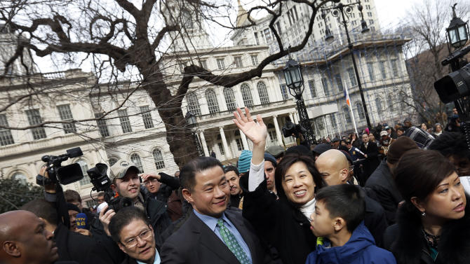 New York City Comptroller John Liu, center, is joined by his wife Jenny, waving, and son Joey, second right, as he greets supporters after announcing the launch of his mayoral campaign on the steps of City Hall, Sunday, March 17, 2013 in New York.  Already the first person of Asian descent to be elected citywide in New York, Liu hopes to become the city's first Asian-American mayor. (AP Photo/Jason DeCrow)