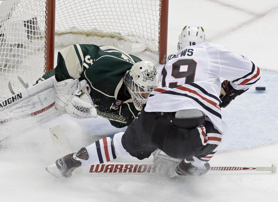 Minnesota Wild goalie Josh Harding, left, stops a shot by Chicago Blackhawks' Jonathan Toews in the first period of Game 4 of an NHL hockey Stanley Cup playoff series, Tuesday, May 7, 2013 in St. Paul, Minn. Harding was injured on the play and left the game after the first period. (AP Photo/Jim Mone)