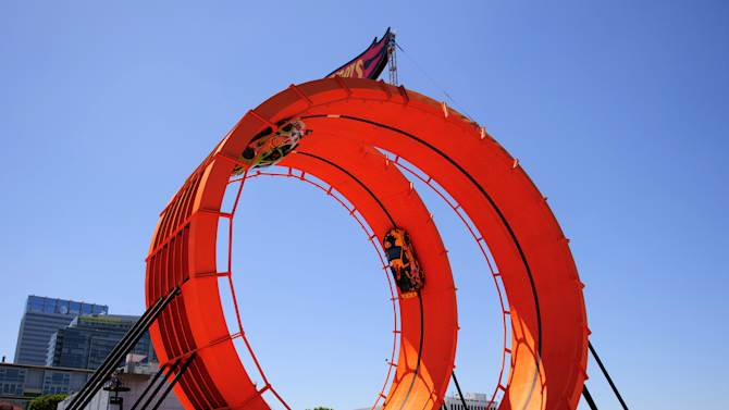 In this handout provided by Mattel, team Hot Wheels green driver Greg Tracy and yellow driver Tanner Foust set Guinness World Records Title by successfully racing through a 60-foot-tall double vertical loop at the X Games Los Angeles on Saturday June 30, 2012 in Los Angeles. (Photo by Max Simbron for Mattel/Invision/AP Images)