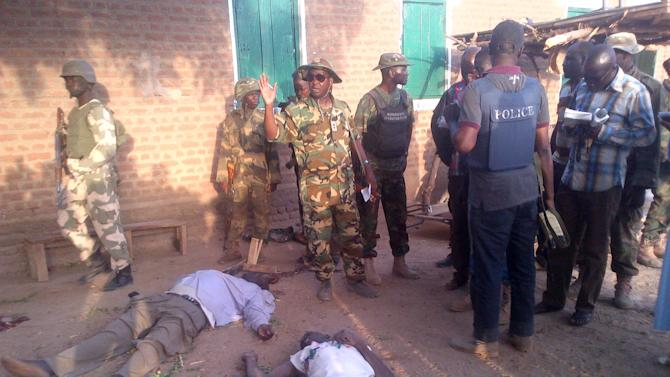In this photo taken with a mobile phone, Tuesday, May. 7, 2013, soldiers  and journalist looks at bodies of prison officials killed by Islamic extremist  during  heavy fighting in Bama, Nigeria. Coordinated attacks by Islamic extremists armed with heavy machine guns killed at least 42 people in northeast Nigeria, authorities said Tuesday, the latest in a string of increasingly bloody attacks threatening peace in Africa's most populous nation. The attack struck multiple locations in the hard-hit town of Bama in Nigeria's Borno state, where shootings and bombings have continued unstopped since an insurgency began there in 2010. Fighters raided a federal prison during their assault as well, freeing 105 inmates in another mass prison break to hit the country, officials said. (AP Photo/Abdukareem Haruna)