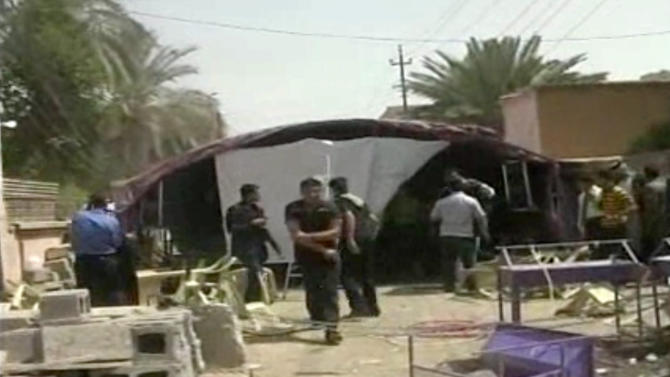 This image from AP video shows the aftermath of a suicide attack in Baqouba, some 60 kilometers (35 miles) northeast of Baghdad, Iraq, Saturday, April 6, 2013. A suicide bomber blew himself up Saturday at a lunch hosted by a Sunni candidate in Iraq's upcoming regional elections, killing scores of people, officials said. The blast ripped through a hospitality tent pitched next to the house of Muthana al-Jourani, who is running for the provincial council and held the lunch rally for supporters, councilman Sadiq al-Huseini said. (AP Photo via AP video)
