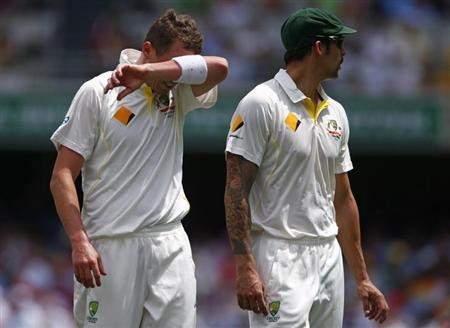 Australia's Peter Siddle (L) reacts next to teammate Mitchell Johnson after dropping a catch played by England's Kevin Pietersen during the second day's play of the first Ashes cricket test match in B