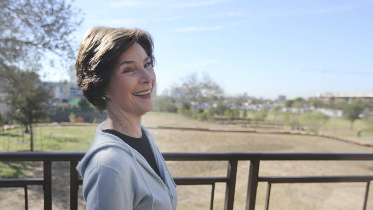 In this Monday, Oct. 29, 2012 photo, former first lady Laura Bush smiles during a tour of the George W. Bush Presidential Center in Dallas.  A 15-acre park at the upcoming George W. Bush Presidential Center will recreate a Texas prairie, complete with a wildflower meadow, a special blend of native grasses and even trees transplanted from the former president's ranch. The park's landscaping, which was completed this month, is a recreation of the kind of prairie landscape that would have existed in the area before it the city was built. (AP Photo/LM Otero)