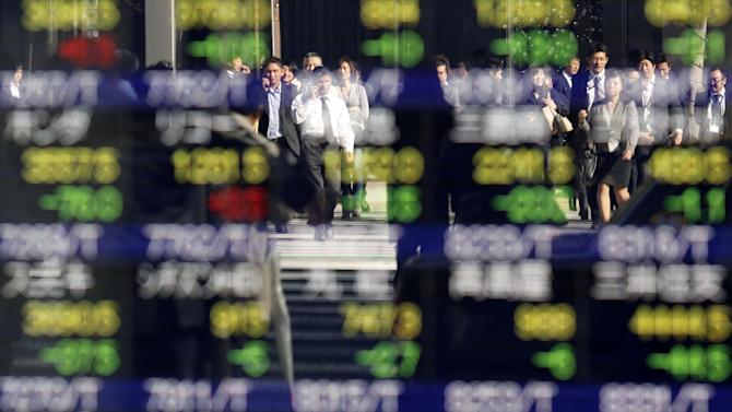 People are reflected on an electronic stock indicator of a securities firm in Tokyo Thursday, Nov. 27, 2014. Asian shares were mostly higher Thursday on hopes for more stimulus in China. Japan's Nikkei 225 dropped 0.3 percent to 17,333.52. (AP Photo/Shuji Kajiyama)