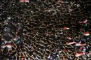Egyptian protesters wave their hands and hold national flags during anti-President Mohammed Morsi demonstration in Tahrir Square, the focal point of Egyptian uprising in Cairo, Egypt, Friday, June 28, 2013. Tens of thousands of backers and opponents of Egypt's Islamist president held competing rallies in the capital Friday and new clashes erupted between the two sides in the country's second largest city, Alexandria, in a prelude to massive nationwide protests planned by the opposition this weekend demanding Mohammed Morsi's removal.(AP Photo/Amr Nabil)