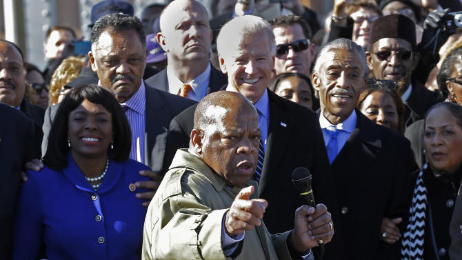 U.S. Rep. John Lewis, D-Ga., points to where he and others were beaten 48 years ago when they tried to cross the Edmund Pettus Bridge during a civil rights march in Selma, Ala., Sunday, March 3, 2013. At rear is Vice President Joe Biden. At left is U/S. Rep. Terri Sewell, D-Ala., Jesse Jackson is second from left. (AP Photo/Dave Martin)