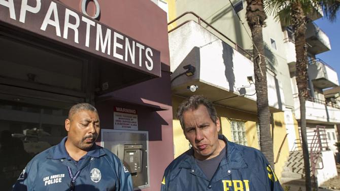 Law enforcement agents, LAPD Sgt. Anthony Verret, left, and FBI agent Scott Garriola, right, enter the apartment building where LAPD and an FBI task force arrested 26-year-old Ammar Harris, who is accused in the Feb. 21 deaths of three people on the Las Vegas strip, in the Studio City area of Los Angeles, Thursday, Feb. 28, 2013. The 26-year-old is a self-described pimp who was the subject of a multi-state manhunt following the Feb. 21 gunfire and chain-reaction crash that killed three and injured at least five. (AP Photo/Damian Dovarganes)