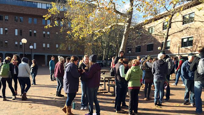Students gather on the Western Washington University campus in Bellingham, Wash., after classes were canceled ,Tuesday, Nov. 24, 2015, because of threats over the weekend against minorities posted on YikYak, an anonymous social media platform populated by college students. (Perry Blankinship via AP)